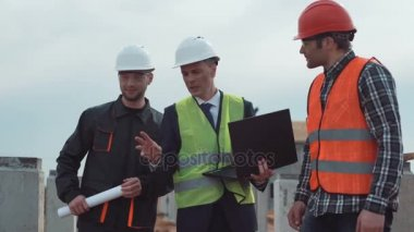Men on building site discussing the blueprint