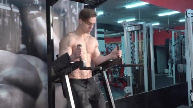 Young man making abdominal exercises in gym