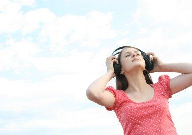 Girl standing with black big headphones