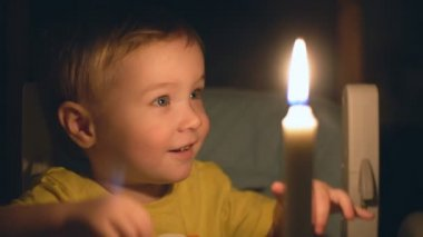 Little boy blowing on a candle. 4K