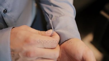Young businessman getting dressed at morning. Man buttons cuffs on shirt, putting his suit. Close-up view of male hands.