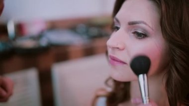The makeup artist applies with a brush, uses blush. Close-up view of young beautiful girl waiting for a make-up.