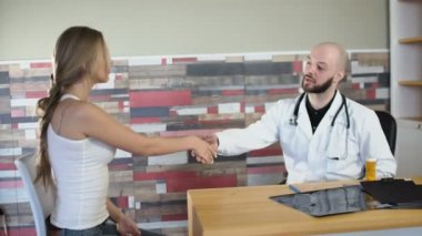 30s bearded doctor make Gesture of encouragement taking hand of a female girl patient at medical office shake her hand and calm her down 4k