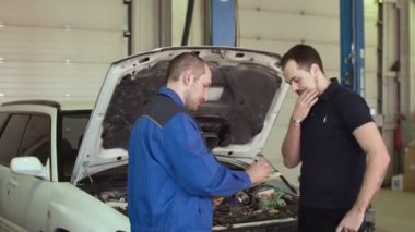 Car mechanic is discussing with client in auto repair service with clipboard behind opened hood of a car