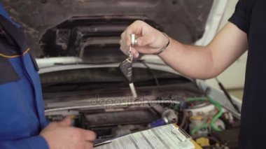 Close up of hands client of repair car service is giving keys to car mechanic with clipboard and shaking hands