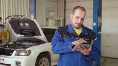 Car mechanic using tablet touch screen on a car cepair service