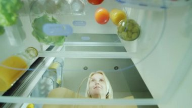 A young woman loads the food in the fridge. Opens the door of the refrigerator and puts there just bought vegetables. Inside view