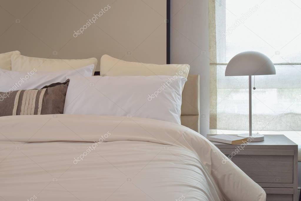 베개와 침대 옆 테이블에 독서 용 램프와 아늑한 침실 인테리어 ...