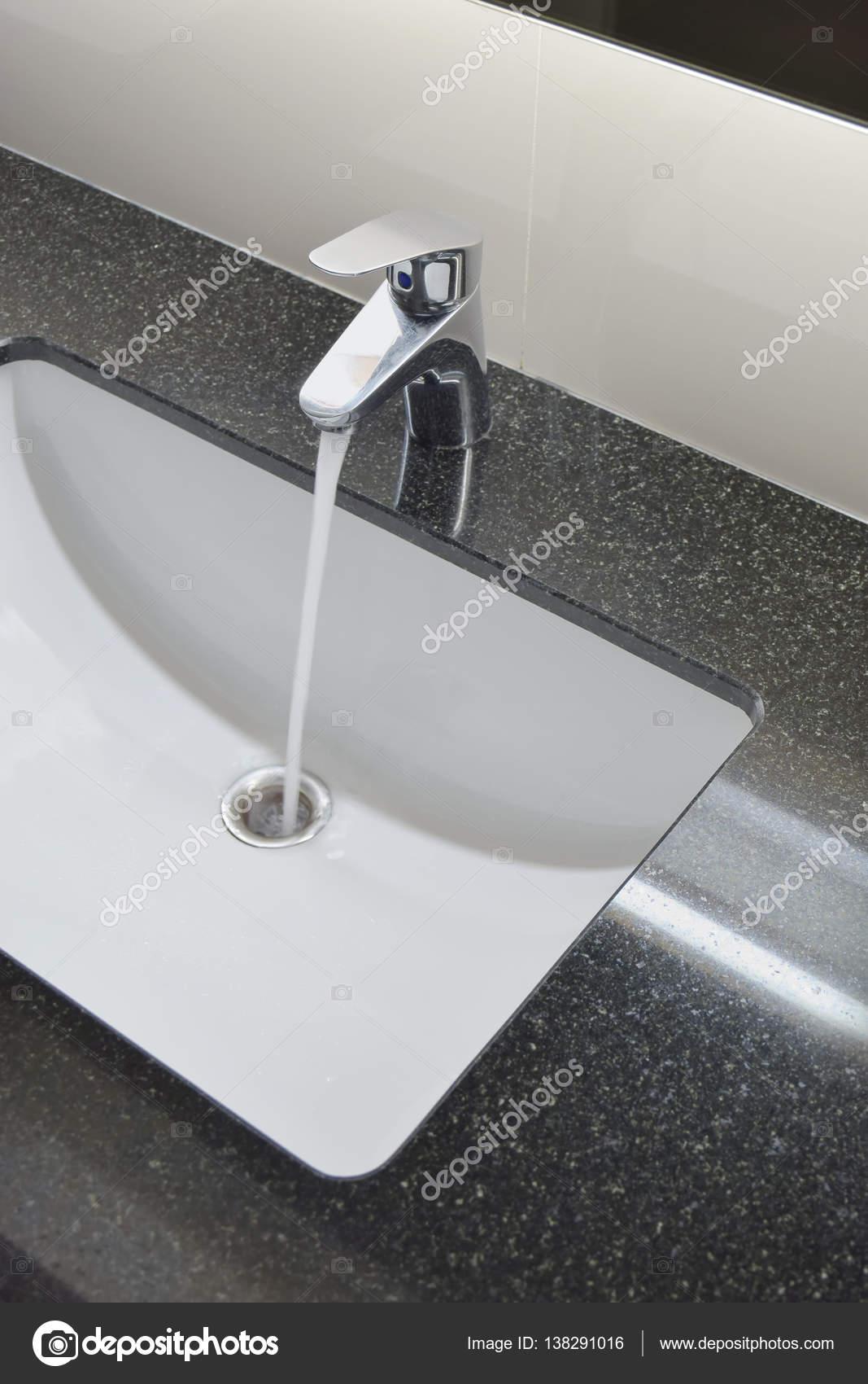 grifo y lavabo mostrador con encimera de granito negro u foto de stock
