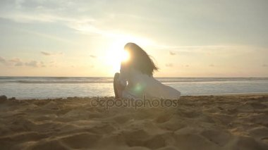 Beautiful young girl sitting on the ocean beach at sunset time. Woman sitting on the golden sand at sea shore and looking to sundown over waves. Rear back view Slow motion
