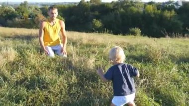 Little child goes on green grass at the field to his father at sunny day. Dad lifting up his baby boy at nature. Happy family on a summer meadow. Toddler learning to walk. Close up.