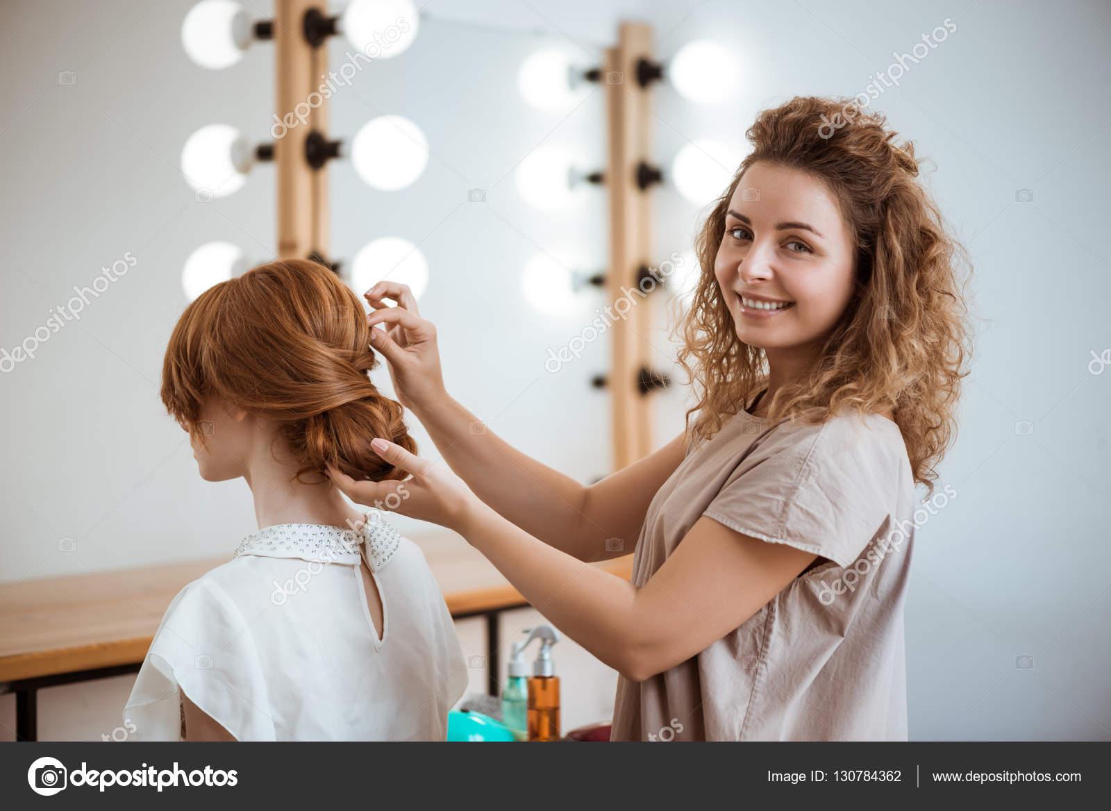 Девушка делает причёску фото