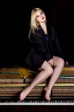 Fashion young woman in a mans jacket, sitting on old retro wooden piano with keyboard and posing
