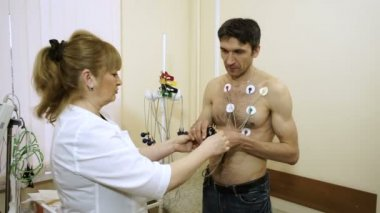 Holter monitor device. Female doctor attaching electrodes on patients chest to daily monitoring of an electrocardiogram. HD