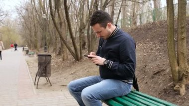 Man sitting on park bench with mobile phone