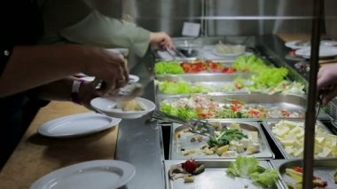 People impose food. Catering. Impose Salad. Food Distribution Table.