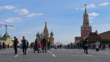 MOSCOW, RUSSIA, April 9, 2017: Tourists are walking along Red Square. Attend tours, photographed against the background of the Kremlin and St. Basils Cathedral.