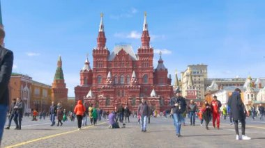 MOSCOW, RUSSIA, April 9, 2017: Tourists and locals, walking around Red Square on a sunny spring day. Photographed against the background of the Kremlin, and the Historical Museum.