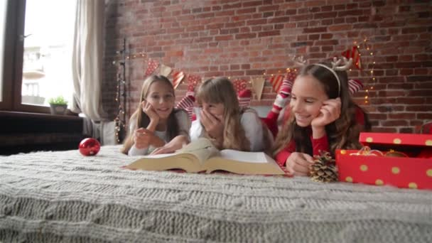 Three sisters lie on the bed in soft pajamas, Triplets read a huge ...