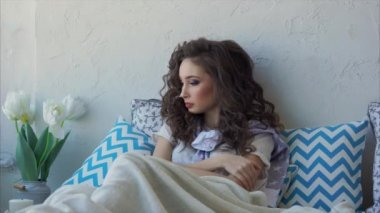 A young woman who has recently woken up, lies on a bed, leaning on a pillow.