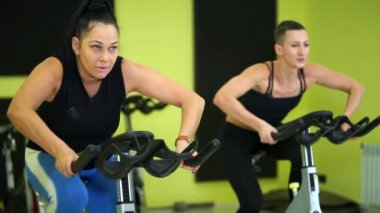 Women are engaged in group bike training to maintain physical fitness.