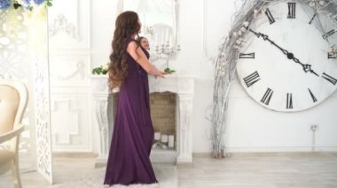 Girl in evening gown smiles on the background luxurious interior