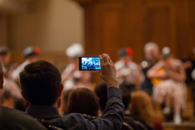 Auditorium at concert - people shooting performance on smartphone, music opera