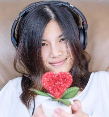 Asian girl is holding heart love flower while listen to music