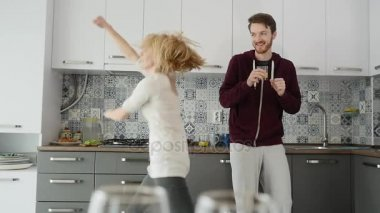 Morning at home happy young couple newly wed dancing listening to music in kitchen