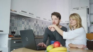 Couple using computer at kitchen counter