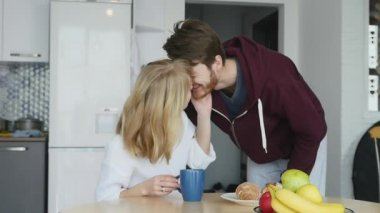 Loving guy hugging his smiling girlfriend in their kitchen early in the morning with breakfast