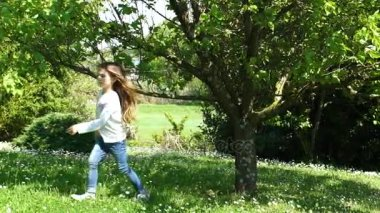 Little girl with long brown hair gathering a fruit from the tree, slow motion HD