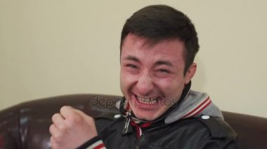 Portrait of a laughing man pointing at camera.