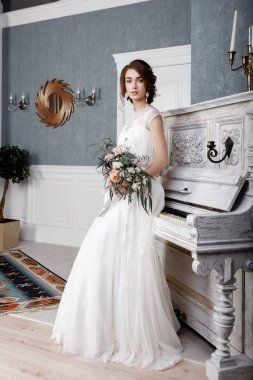 Beautiful bride with bouquet near the White Piano