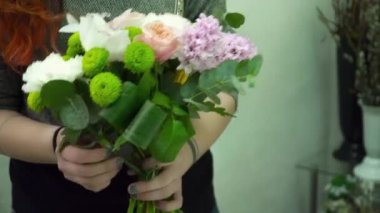 Florist making a beautiful bouquet with the orchids and pink roses