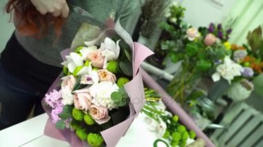 Florist wrapping a bouquet with paper for decoration in flower shop