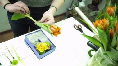 Florist making a bouquet with tulip in the box
