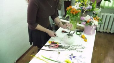 Florist making a bouquet in the gesso pot on the table