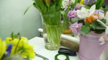 Florist making a bouquet with yellow flowers in the gesso pot on the white wooden table