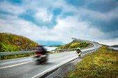 Two bikers on motorcycles. Atlantic Ocean Road or the Atlantic Road (Atlanterhavsveien) been awarded the title as Norwegian Construction of the Century.