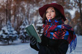 Beautiful young brunette woman reading book wearing knitted poncho, wide hat and coat in the snowy cold and magic winter forest.