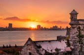 Sunset in Havana with the sun setting over the buildings and el Morro in the foreground
