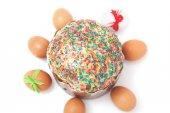Velikonoční vajíčka leží kolem dortu na bílém pozadí