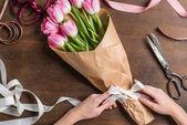 Rózsaszín tulipán és a kezek szalaggal