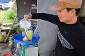 Vietnamský muž dělat cukrové třtiny šťávy z cukrové třtiny pro turisty