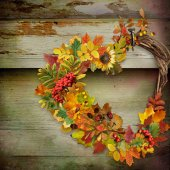 A wreath of autumn leaves and berries in heart shape on wooden background