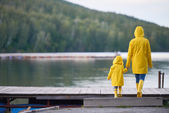 Frau und Kind in gelben Regenmäntel