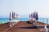 Landscape Lake Garda with pier, beach chairs and umbrellas in the foreground, Italy