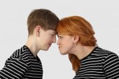 Woman and teenage boy resting heads against each other