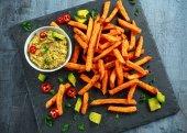 Zdravá domácí pečený pomeranč sladkými bramborami s guacamole, sůl, pepř na stine, kamenné desky